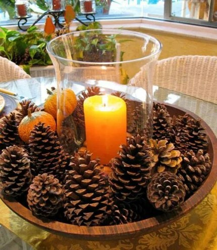 Wooden bowl with pinecones and a vase and candle in the middle.